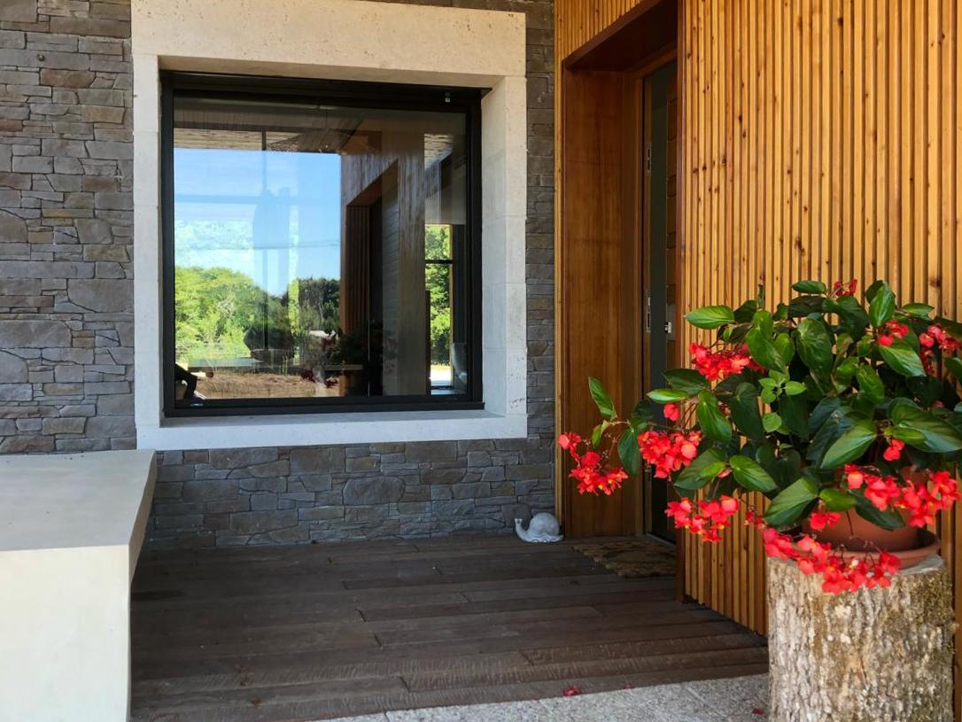Entrée extérieure faite en bois et pierres apparentes d'une maison d'habitation en Périgord. Peintures intérieures et extérieures réalisées par la SARL MArcillac et fils.